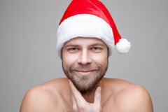 Handsome man with beard wearing a Christmas hat. Portrait of a handsome man with beard wearing a Christmas hat Royalty Free Stock Photography