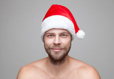 Handsome man with beard wearing a Christmas hat. Portrait of a handsome man with beard wearing a Christmas hat Royalty Free Stock Images