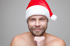 Handsome man with beard wearing a Christmas hat. Portrait of a handsome man with beard wearing a Christmas hat Stock Images