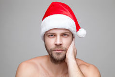 Handsome man with beard wearing a Christmas hat. Portrait of a handsome man with beard wearing a Christmas hat Royalty Free Stock Photo