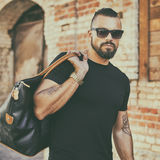 Handsome man with beard wearing sunglasses and holding black bag Royalty Free Stock Photos