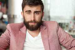 Handsome man with beard . Handsome young elegant man sitting, relaxing, smiling. Men with beard looking at camera. Indoor photo Royalty Free Stock Photography