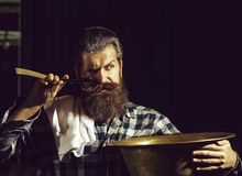 Bearded man shaves with razor. Handsome man, bearded hipster, brunette with long beard and moustache shaves with open vintage razor with blade and copper basin royalty free stock photos