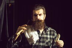 Bearded man shaves with razor. Handsome man, bearded hipster, brunette with long beard and moustache shaves with open vintage razor with blade and shaving brush royalty free stock image