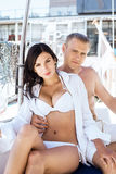 Handsome man and a beautiful and sexy woman on a sailing boat. Handsome and rich men and a beautiful and sexy women in swimsuit relaxing on a sailing boat Stock Photography