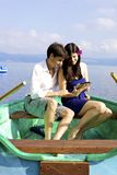 Handsome man with beautiful woman on boat with ipad. Happy couple sitting on green boat in vacation reading electronic tablet ipad Royalty Free Stock Photos