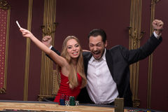 Handsome man and beautiful woman in casino Stock Image
