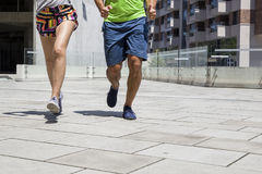 Handsome man and beautiful woman jogging together on street betw Stock Photos