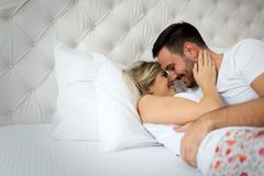 Handsome man and beautiful woman kissing on bed. Handsome men and beautiful women kissing each other on bed Stock Photo