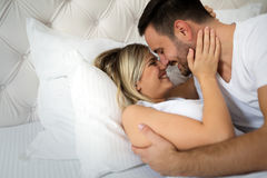 Handsome man and beautiful woman kissing each other. Handsome men and beautiful women kissing each other on bed Stock Photography