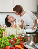 Handsome man and beautiful woman with vegetables in the kitchen Stock Photos