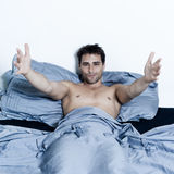 Handsome man in a bed Stock Photography