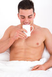 Handsome man in bed enjoys the smell of coffee Royalty Free Stock Images