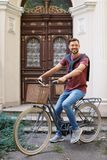 Handsome man with bicycle near ornate door. On street royalty free stock photo