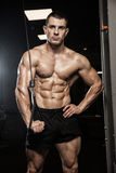 Handsome man with big muscles, posing at the camera in the gym stock photography