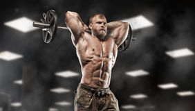 Handsome man with big muscles, posing at the camera in the gym stock photos