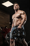 Handsome man with big muscles, posing at the camera in the gym Royalty Free Stock Images
