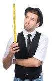 Handsome man in black hat rating the measure tape data. Isolated Stock Image