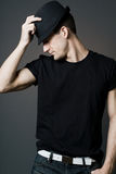 Handsome man in black shirt holding black hat. Stock Photos