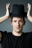 Handsome man in black shirt holding black hat. Royalty Free Stock Image