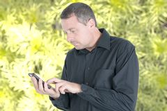 Handsome man in black shirt outdoor texting in cell smartphone royalty free stock photos