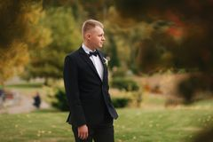 Handsome man in black suit standing outside in autumn. Groom waiting for bride.  stock images