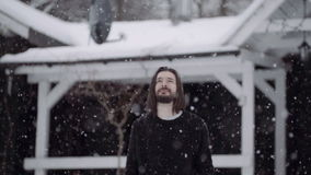 Handsome man in black sweater standing in front of an old wooden house among falling snow. stock footage