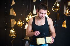 Handsome man in black tank top holds a gift in her hands, opens a gift, present. Handsome young man posing in studio, model photo. holds a gift in his hands Royalty Free Stock Photos