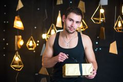 Handsome man in black tank top holds a gift in her hands, opens a gift, present. Handsome young man posing in studio, model photo. holds a gift in his hands Royalty Free Stock Photography