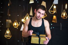 Handsome man in black tank top holds a gift in her hands, opens a gift, present. Handsome young man posing in studio, model photo. holds a gift in his hands Stock Images