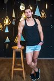 Handsome man in black tank top, posing, fashion portrait. Handsome young man with a beard and in a black T-shirt posing on a black background Royalty Free Stock Images