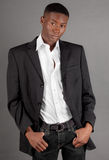 Handsome Man in Blazer. A portrait of a young black man in a blazer and jeans royalty free stock images