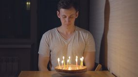 Handsome man blowing out candles on holiday cake.  stock video footage
