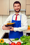 Handsome man in blue apron holding pan Stock Image