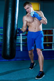 Handsome man in blue boxing gloves training on a punching bag in the gym. Male boxer doing workout. Handsome man in blue boxing gloves training on a punching Royalty Free Stock Images