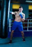Handsome man in blue boxing gloves training on a punching bag in the gym. Male boxer doing workout. Stock Image