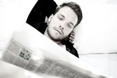 Handsome man with blue eyes lies in bed with white sheets reading paper Royalty Free Stock Photos