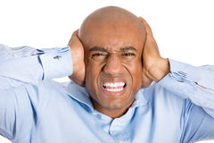 Handsome man with blue shirt and covering his ears Royalty Free Stock Photos