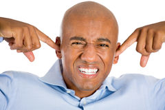 Handsome man with blue shirt and covering his ears, headache from loud noise Royalty Free Stock Photo