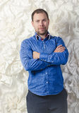 Handsome man in blue shirt posing against decorated wall Royalty Free Stock Photography