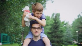 Handsome man in blue shirt walking on the street with his son. Male parent showing to child urban landscape. Boy sitting. Handsome man with eyeglasses dressed in stock footage
