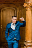 Handsome man in blue suit and bow tie standing at old luxury wooden interior Royalty Free Stock Photography