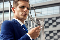 Portrait of a male model smokes a cigarette. A handsome man in a blue suit and tie is holding a cigarette in his hand Stock Photography