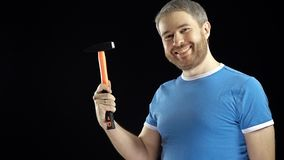 Handsome man in blue tshirt holds hammer. DIY, repair, amateur construction or home improvement concepts. Black. Handsome man in blue tshirt holds hammer. DIY royalty free stock images