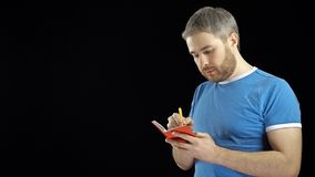 Handsome man in blue tshirt writing in his red notebook. Memo, search or contact concepts. Black background Royalty Free Stock Photo