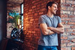 A handsome man with BMX in a studio. A stylish tattoed attractive man dressed in jeans and a t-shirt, leans against the brick wall, with his arms crossed stock photography