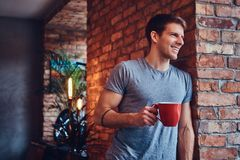 A handsome man with BMX in a studio. A stylish tattoed attractive man dressed in jeans and a t-shirt, leans against the brick wall, holding a cup of coffee royalty free stock photos