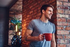 A handsome man with BMX in a studio. A stylish tattoed attractive man dressed in jeans and a t-shirt, leans against the brick wall, holding a cup of coffee royalty free stock photography