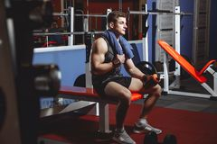 Handsome man with bottle of water and towel having a break after workout in gym. royalty free stock photography