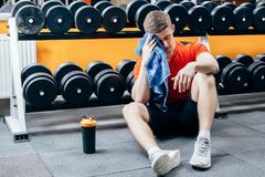 Handsome man with bottle of water and towel having a break after workout in gym.  Royalty Free Stock Image